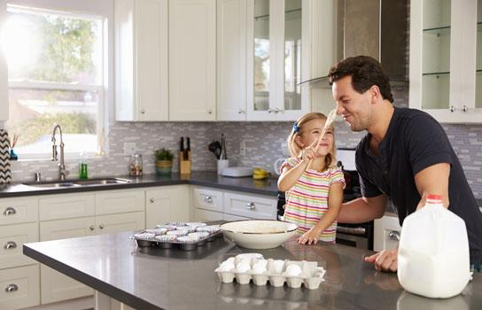 AAA Insurance - peace of mind. Happy dad and daughter baking in kitchen.