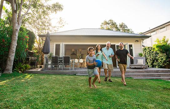 Get a home/renters quote - family playing in the yard, front of house in the summer