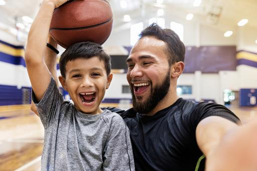 AAA Life -  Smiling father and son playing basketball in a gym.