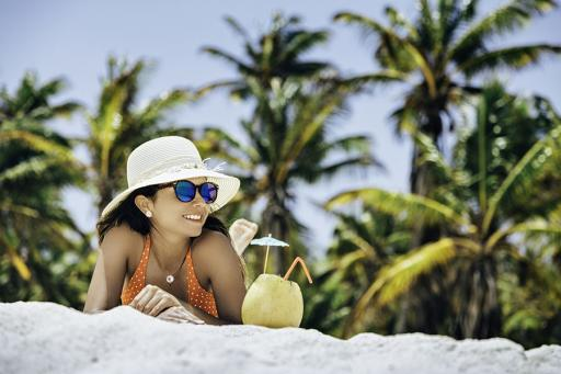 Lady on beach, white sand and palm trees