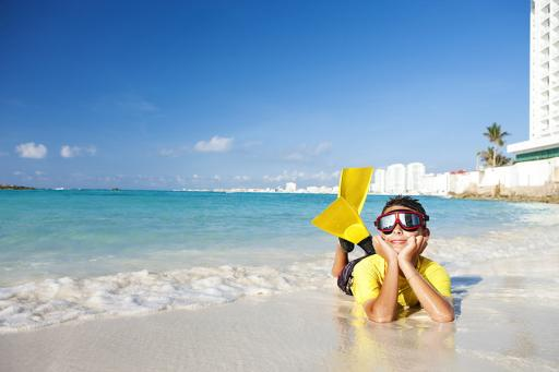 Boy on beach with snorkel and fins.