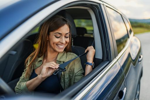 AAA Auto Insurance - Smiling lady buckling aseat belt in her car.