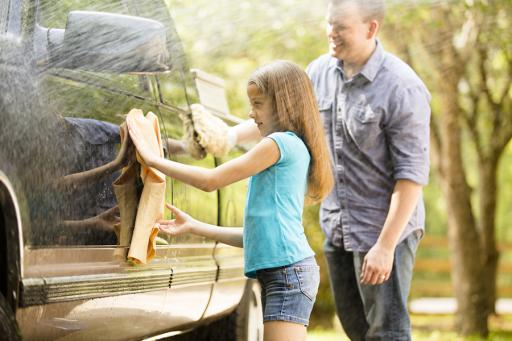 Insurance, father and daughter outside washing a black truck