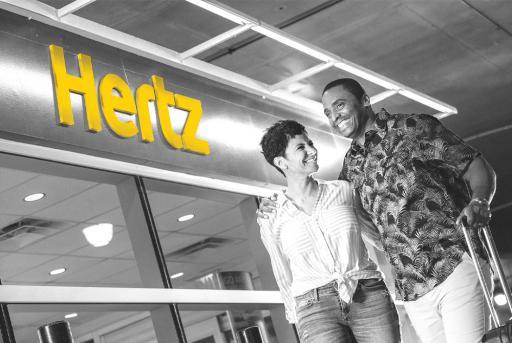 Hertz Gold couple near Hertz sign