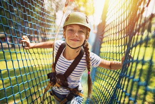 Smiling girl walking net rope